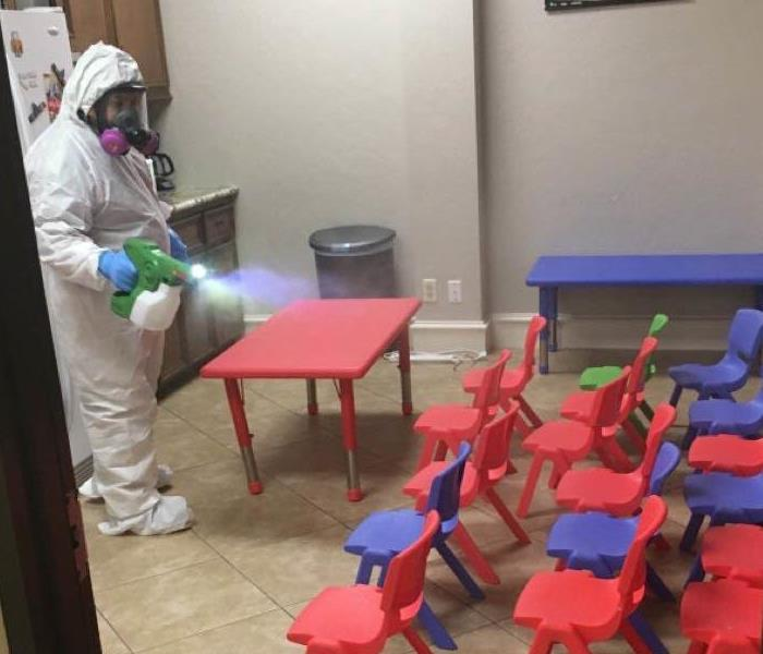 Worker disinfects empty classroom or daycare