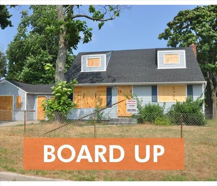 board up Blue cape cod style suburban home